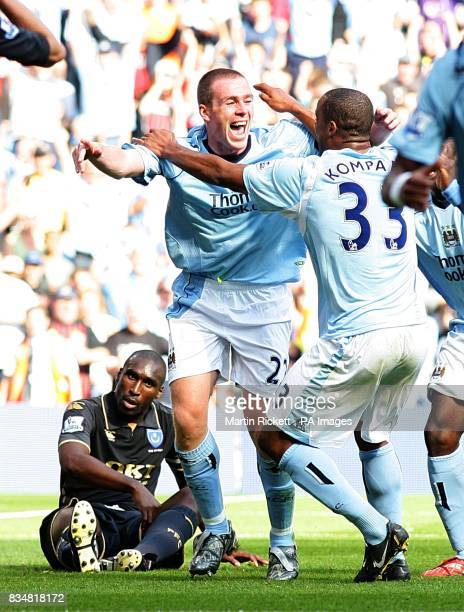 Manchester City's Richard Dunne celebrates scoring his sides second goal of the game with teammate Vincent Kompany