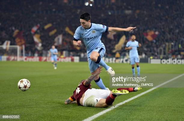 Manchester City's Samir Nasri jumps clear of a challenge from AS Roma's Radja Nainggolan