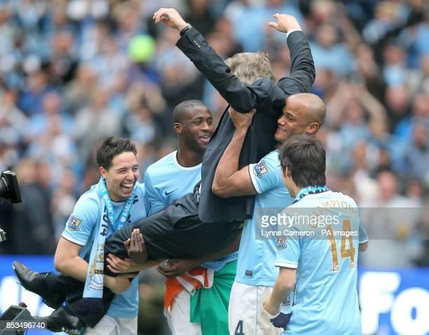 Manchester City's Samir Nasri Yaya Toure Vincent Kompany and David Silva enjoy lifting manager Manuel Pellegrini aboove their heads during the post...
