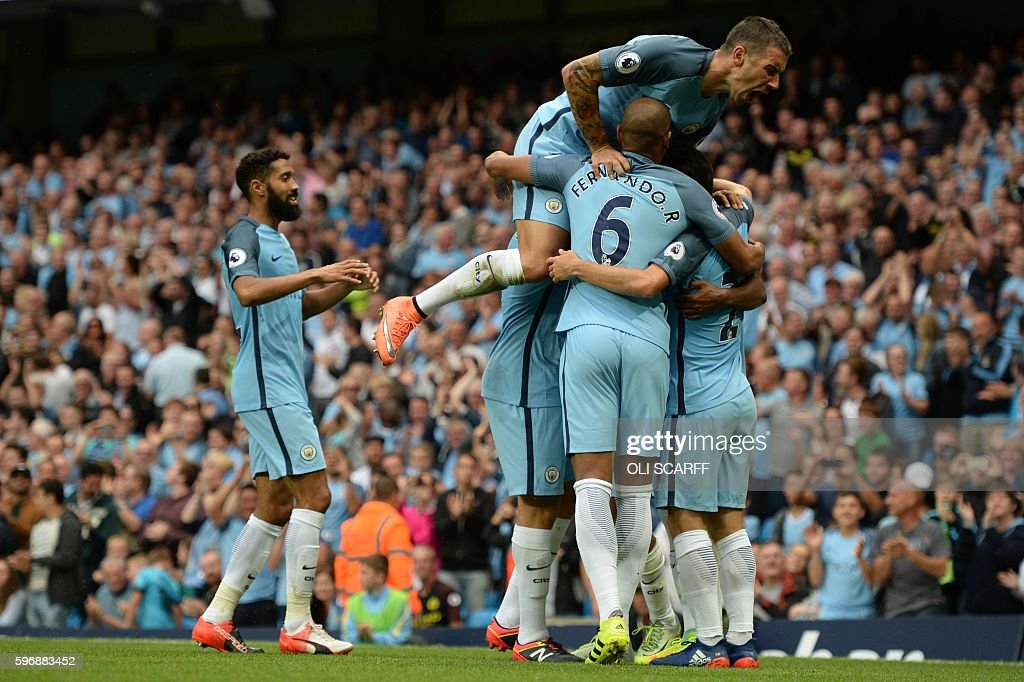 Manchester City's Serbian defender Aleksandar Kolarov jumps on teammates after Manchester City's English midfielder Raheem Sterling scored during the...