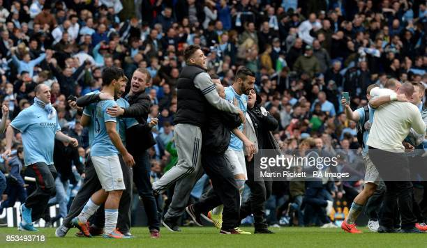 Manchester City's Sergio Aguero and Alvaro Negredo are surrounded by fans as they invade the pitch at the final whistle after winning the Premier...