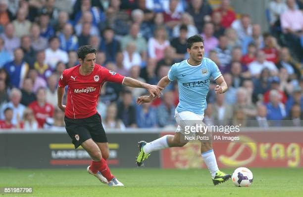 Manchester City's Sergio Aguero and Cardiff City's Peter Whittingham battle for the ball