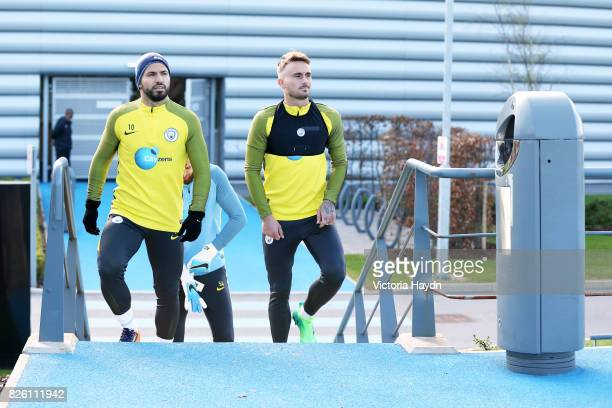 Manchester City's Sergio Aguero and /Manchester City's Aleix Garcia walk out to the training ground