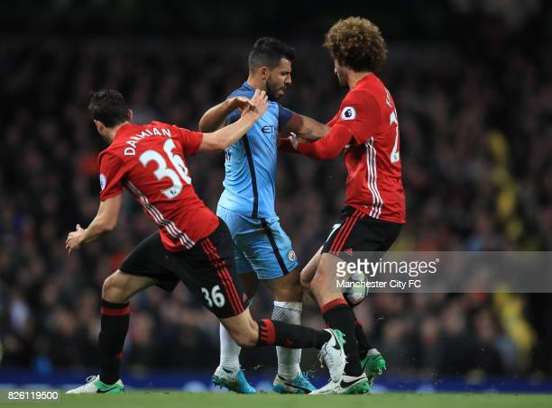 Manchester City's Sergio Aguero battle for the ball against Manchester United's Matteo Darmian and Manchester United's Marouane Fellaini