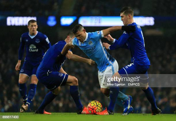 Manchester City's Sergio Aguero goes down in the box after a challenge from Everton's John Stones and Phil Jagielka