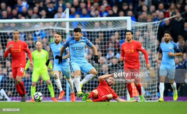 Manchester City's Sergio Aguero jumps over a challenge from Liverpool's Adam Lallana