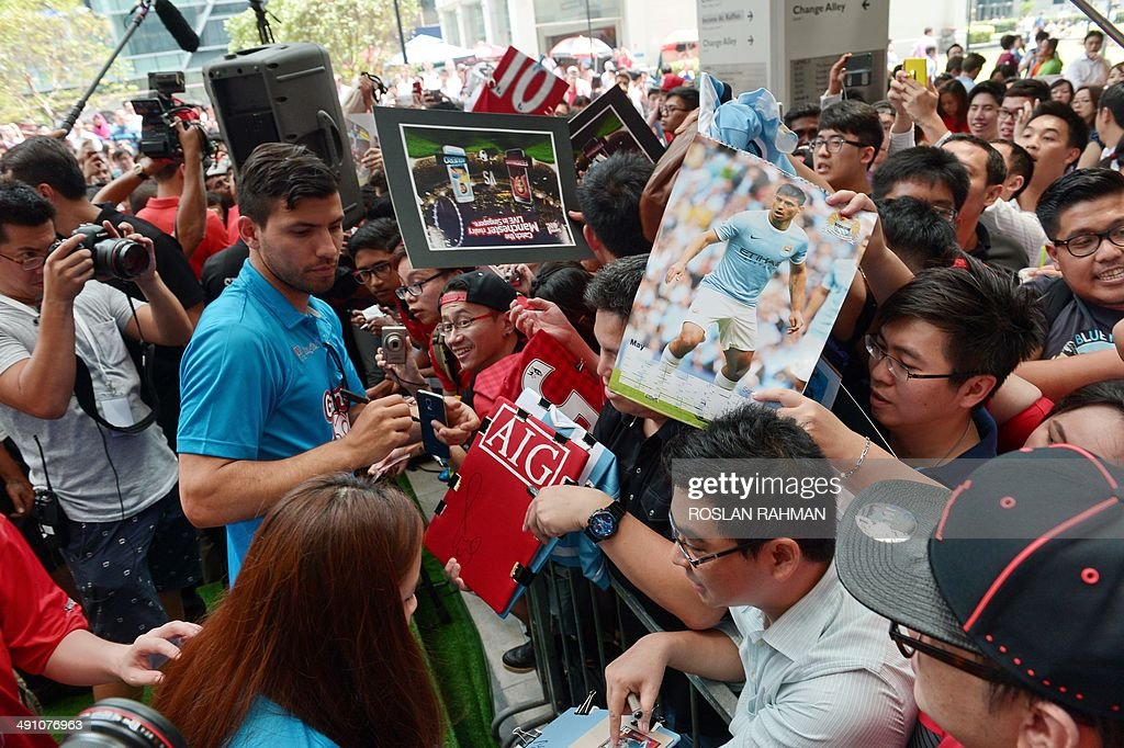 Manchester City's Sergio Aguero (L) signs authograph for fans at the football carnival at Raffles place financial district in Singapore on May 16, 2014 for the SG Game ON! Ultimate Selfie Challenge. SG Game On! is a two-day contest aimed at celebrating Singapore's passion for football in the lead up to the 2014 FIFA World Cup.
