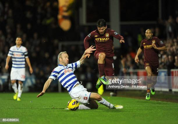 Manchester City's Shaun Derry slides in on Manchester City's Sergio Aguero