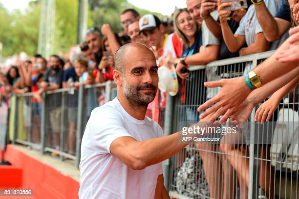 Manchester City's Spanish coach Pep Guardiola cheers Girona supporters before the annual 41st Costa Brava Trophy friendly football match betwen...