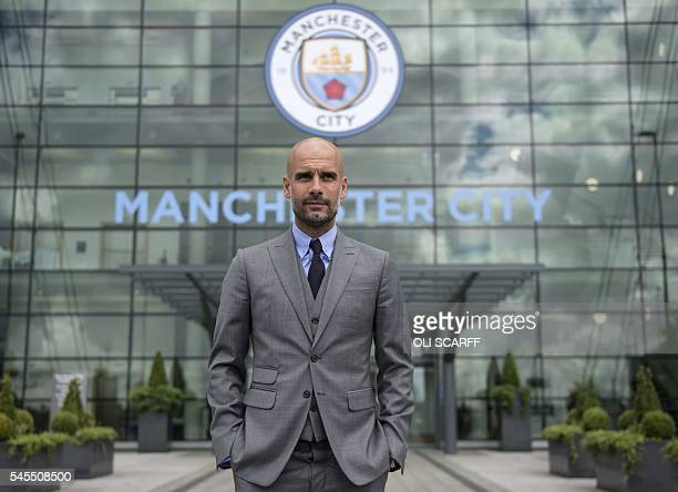 TOPSHOT Manchester City's Spanish football coach Pep Guardiola poses for pictures outside the Etihad Stadium in Manchester northern England on July 8...
