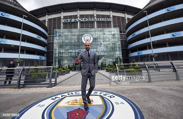 Manchester City's Spanish football coach Pep Guardiola poses for photographs outside the Etihad Stadium in Manchester northern England on July 8 2016...