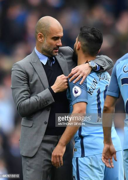 Manchester City's Spanish manager Pep Guardiola and Manchester City's Argentinian striker Sergio Aguero react on the pitch after the English Premier...