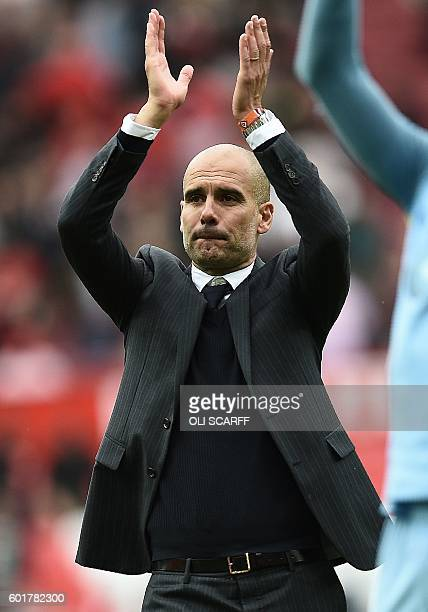 Manchester City's Spanish manager Pep Guardiola celebrates on the pitch after the English Premier League football match between Manchester United and...