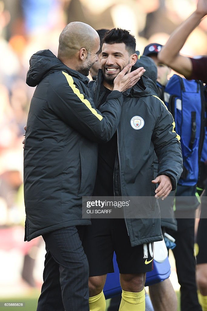 Manchester City's Spanish manager Pep Guardiola (L) celebrates on the pitch with Manchester City's Argentinian striker Sergio Aguero after the English Premier League football match between Burnley and Manchester City at Turf Moor in Burnley, north west England on November 26, 2016. Aguero scored both Manchester City goals as they won the game 2-1. / AFP / Oli SCARFF / RESTRICTED TO EDITORIAL USE. No use with unauthorized audio, video, data, fixture lists, club/league logos or 'live' services. Online in-match use limited to 75 images, no video emulation. No use in betting, games or single club/league/player publications. /