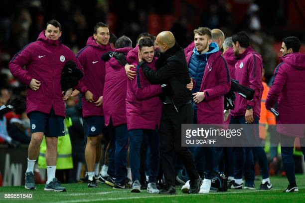 Manchester City's Spanish manager Pep Guardiola celebrates with Manchester City's English midfielder Phil Foden at the end of the English Premier...