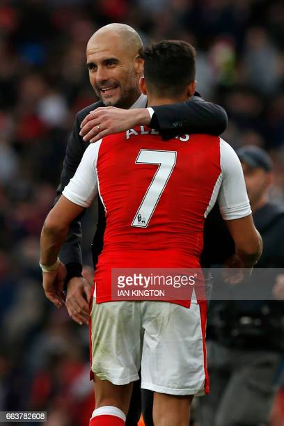Manchester City's Spanish manager Pep Guardiola embraces Arsenal's Chilean striker Alexis Sanchez on the pitch after the English Premier League...