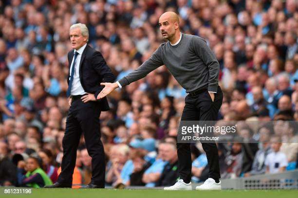 Manchester City's Spanish manager Pep Guardiola gestures from the touchline next to Stoke City's Welsh manager Mark Hughes during the English Premier...