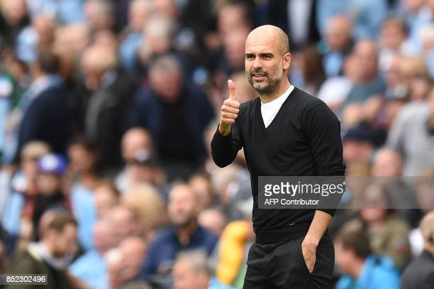 Manchester City's Spanish manager Pep Guardiola gives a thumbs up after City scored their second goal during the English Premier League football...
