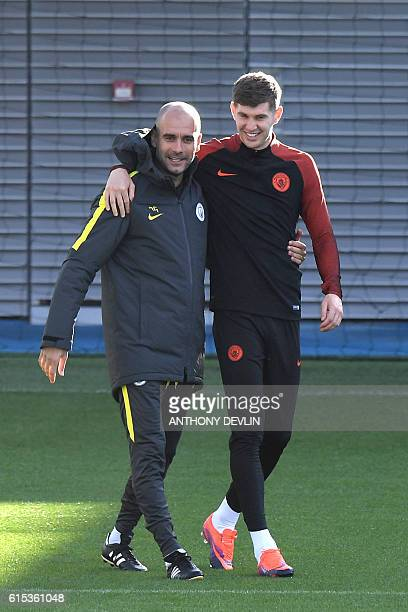 Manchester City's Spanish manager Pep Guardiola hugs England's defender John Stones during a team training session at Manchester City Football...