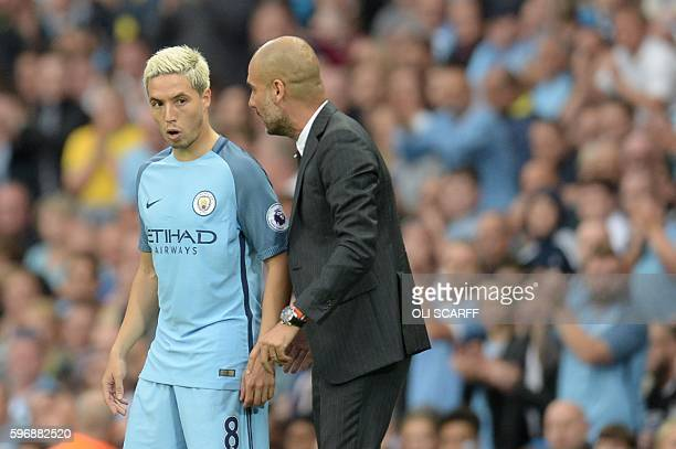 Manchester City's Spanish manager Pep Guardiola talks to Manchester City's French midfielder Samir Nasri as he prepares to come on during the English...