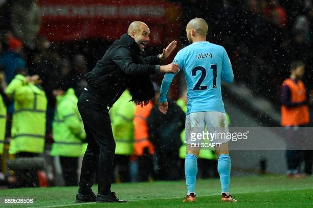 Manchester City's Spanish manager Pep Guardiola talks with Manchester City's Spanish midfielder David Silva during the English Premier League...