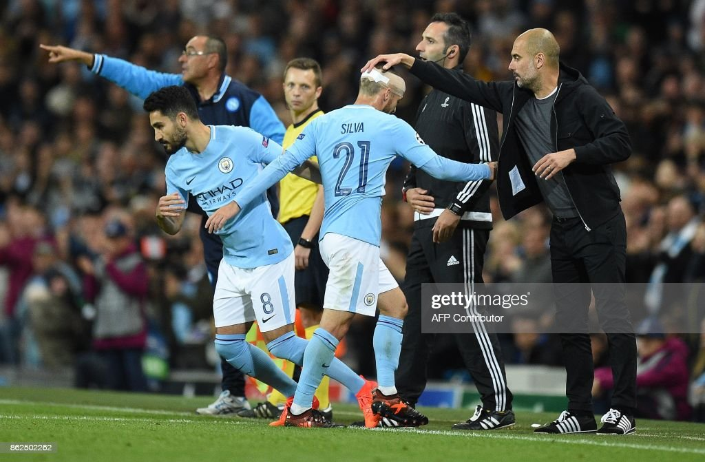 TOPSHOT - Manchester City's Spanish manager Pep Guardiola (R) taps Manchester City's Spanish midfielder David Silva on the head as he is substituted for Manchester City's German midfielder Ilkay Gundogan uring the UEFA Champions League Group F football match between Manchester City and Napoli at the Etihad Stadium in Manchester, north west England, on October 17, 2017. / AFP PHOTO / Oli SCARFF