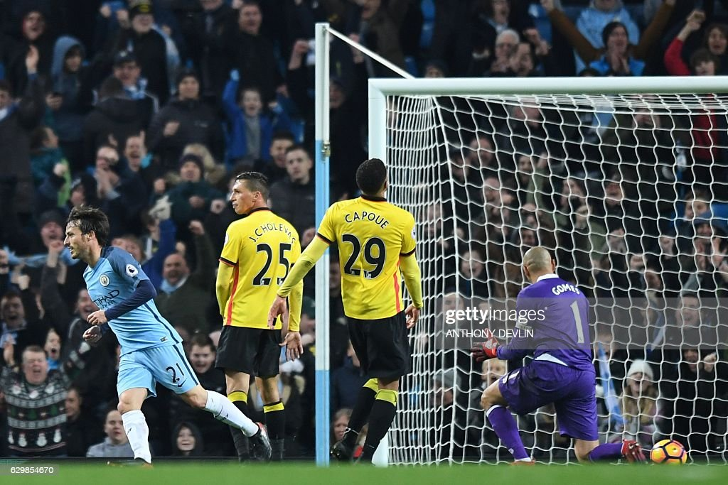 Manchester City's Spanish midfielder David Silva (L) celebrates scoring his team's second goal during the English Premier League football match between Manchester City and Watford at the Etihad Stadium in Manchester, north west England, on December 14, 2016. / AFP / Anthony DEVLIN / RESTRICTED TO EDITORIAL USE. No use with unauthorized audio, video, data, fixture lists, club/league logos or 'live' services. Online in-match use limited to 75 images, no video emulation. No use in betting, games or single club/league/player publications. /