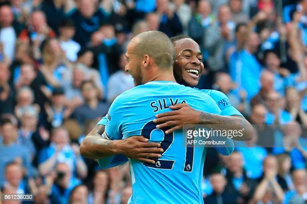 Manchester City's Spanish midfielder David Silva celebrates scoring their third goal with England's midfielder Raheem Sterling during the English...