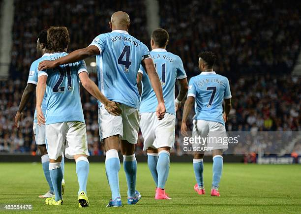 Manchester City's Spanish midfielder David Silva celebrates with Manchester City's Belgian defender Vincent Kompany after he scored during the...