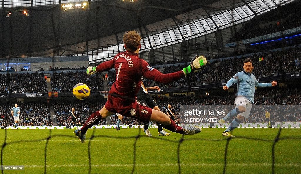 """Manchester City's Spanish midfielder David Silva (R) scores the opening goal past Fulham's Australian goalkeeper Mark Schwarzer during the English Premier League football match between Manchester City and Fulham at The Etihad stadium in Manchester, north-west England on January 19, 2013. AFP PHOTO/Andrew YATES - RESTRICTED TO EDITORIAL USE. No use with unauthorized audio, video, data, fixture lists, club/league logos or """"live"""" services. Online in-match use limited to 45 images, no video emulation. No use in betting, games or single club/league/player publications."""
