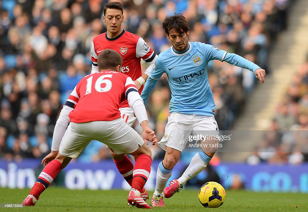 Manchester City's Spanish midfielder David Silva (R) vies with Arsenal's German midfielder Mesut Ozil (C) and Arsenal's Welsh midfielder Aaron Ramsey (L) during the English Premier League football match between Manchester City and Arsenal at the Etihad Stadium in Manchester, northwest England, on December 14, 2013. AFP PHOTO / ANDREW YATES USE. No use with unauthorized audio, video, data, fixture lists, club/league logos or live services. Online in-match use limited to 45 images, no video emulation. No use in betting, games or single club/league/player publications.
