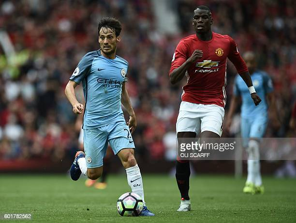 Manchester City's Spanish midfielder David Silva vies with Manchester United's French midfielder Paul Pogba during the English Premier League...