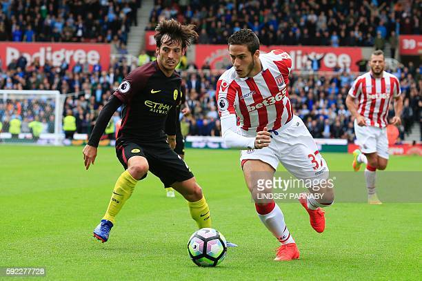Manchester City's Spanish midfielder David Silva vies with Stoke City's Egyptian midfielder Ramadan Sobhi during the English Premier League football...