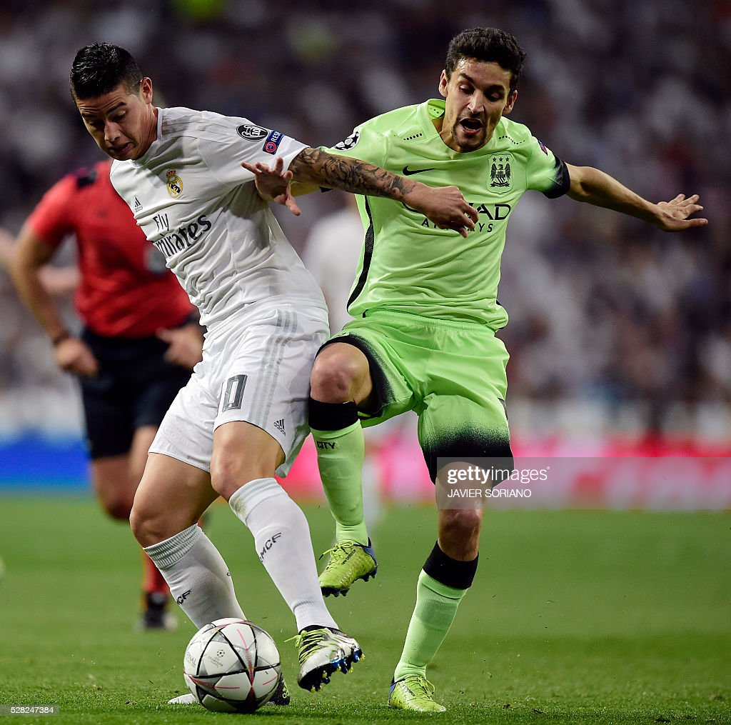Manchester City's Spanish midfielder Jesus Navas (R) vies with Real Madrid's Colombian midfielder James Rodriguez during the UEFA Champions League semi-final second leg football match Real Madrid CF vs Manchester City FC at the Santiago Bernabeu stadium in Madrid, on May 4, 2016. / AFP / JAVIER