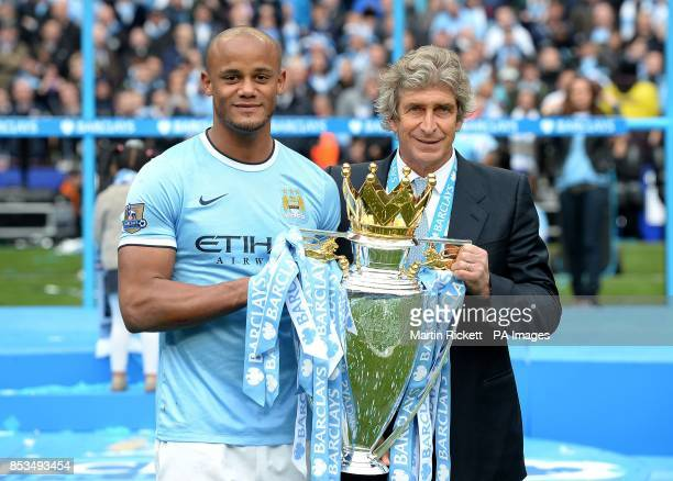 Manchester City's Vincent Kompany and manager Manuel Pellegrini hold the Premier League Trophy following the Barclays Premier League match at the...