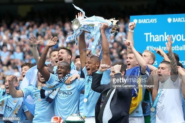 Manchester City's Vincent Kompany lifts the Barclays Premier League trophy after the final whistle