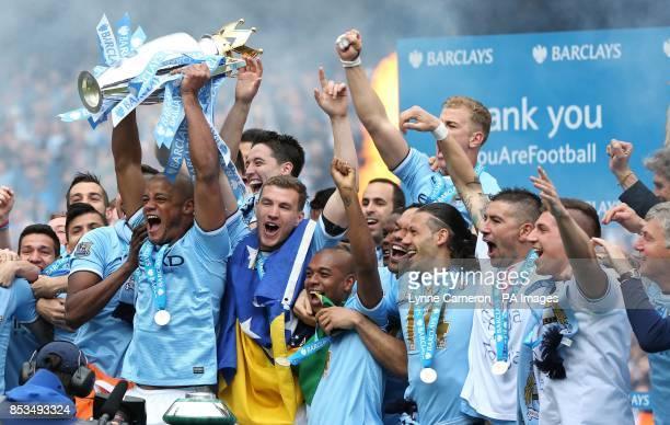 Manchester City's Vincent Kompany lifts the Barclays Premier League trophy following the Barclays Premier League match at the Etihad Stadium...
