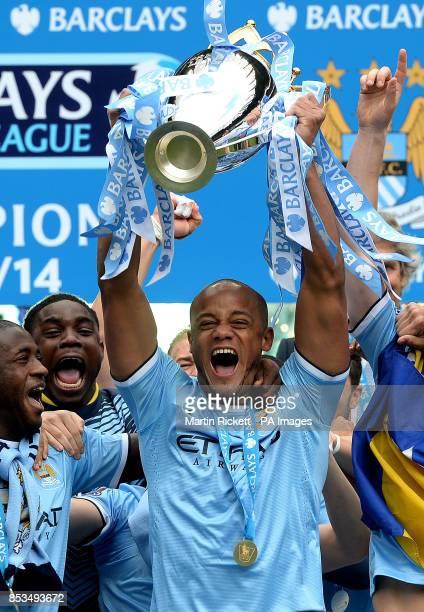 Manchester City's Vincent Kompany lifts the Premier League Trophy after the Barclays Premier League match at the Etihad Stadium Manchester