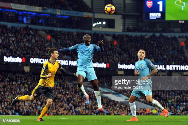 Manchester City's Yaya Toure and Aleksandar Kolarov and Arsenal's Laurent Koscielny in action during the Barclay's Premiership match at the Etihad...