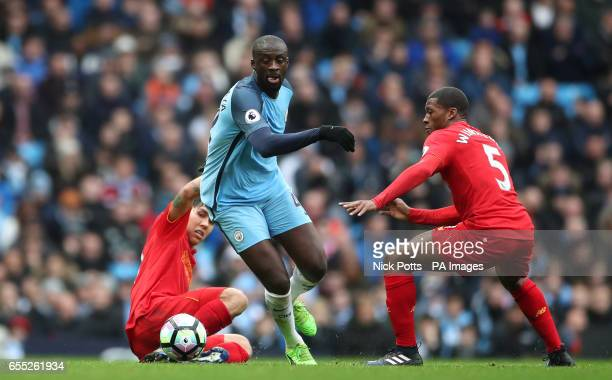 Manchester City's Yaya Toure battles for the ball Liverpool's Georginio Wijnaldum and Roberto Firmino during the Premier League match at the Etihad...