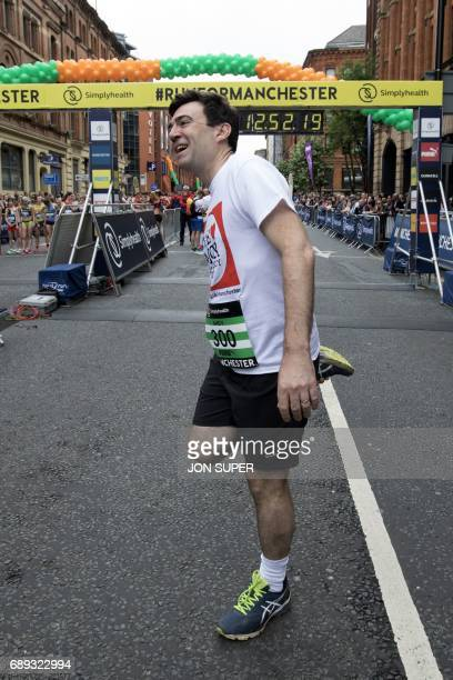 Manchester mayor Andy Burnham does stretching exercises at the start of the Great Manchester Run in Manchester north west England on May 28 2017...