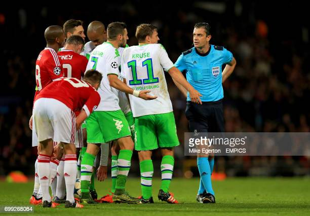 Manchester United and VfL Wolfsburg players speak with referee Viktor Kassai