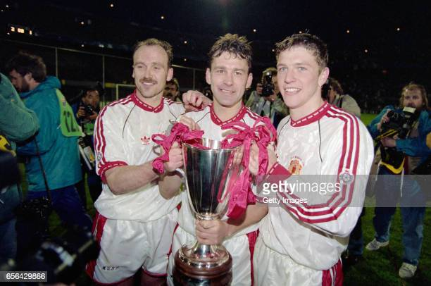 Manchester United captain Bryan Robson celebrates with the trophy with team mates Mike Phelan and Lee Sharpe after the 1991 UEFA European Cup Winners...
