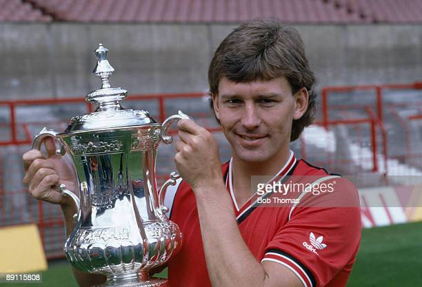 Manchester United captain Bryan Robson holding the FA Cup at their preseason photocall at Old Trafford in Manchester August 1985
