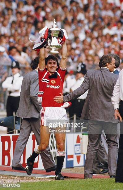 Manchester United captain Bryan Robson holds the trophy aloft as manager Ron Atkinson congratulates him after the 1985 FA Cup Final between...