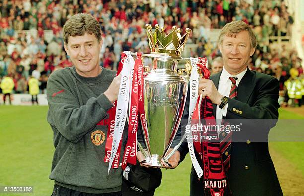 Manchester United coach Brian Kidd and manager Alex Ferguson celebrate with the premiership trophy after winning the 1995/96 title after the FA...