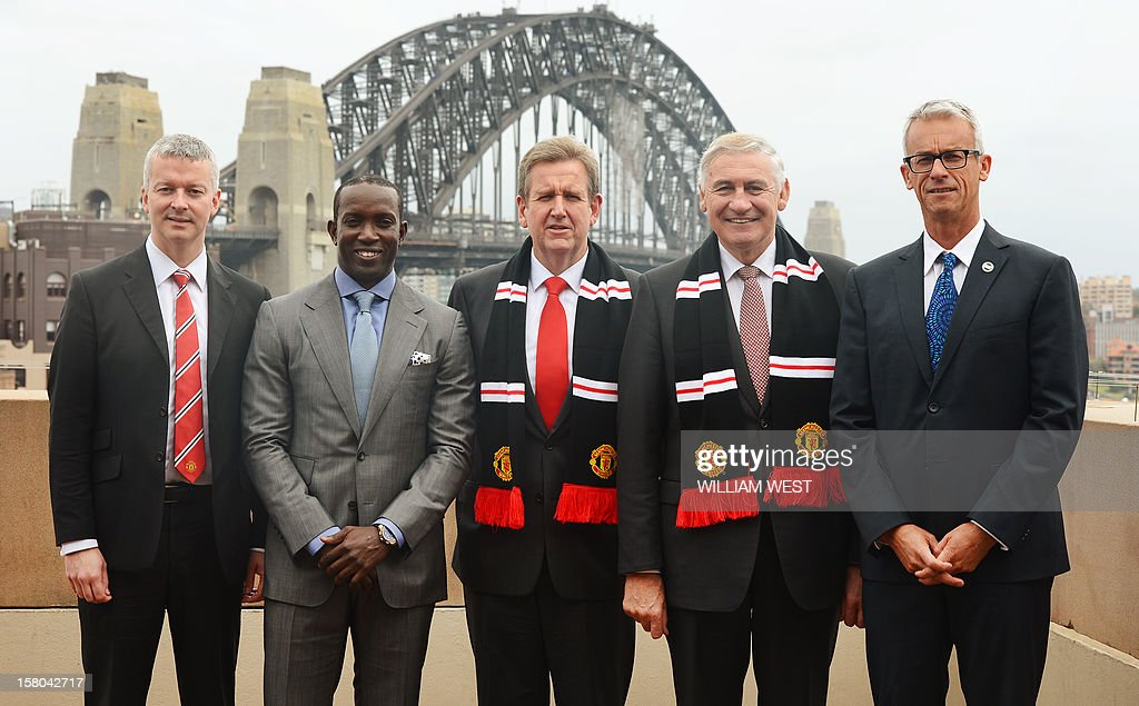 Manchester United Communications Director Phil Townsend (L), former Manchester United player Dwight Yorke (2/L), New South Wales Premier Barry O'Farrell (C), George Souris, Minister for Tourism, Major Events, Hospitality (2/R) and RacingFootball Federation Australia (FFA) CEO David Gallop (R) pose for a photo after a press conference in Sydney on December 10, 2012, as it is announced English Premier League team Manchester United will play an Australian A-League All Stars team in a one-off game in 2013. The match at Sydney's Olympic stadium on July 20, 2013 will be United's first match Down Under in 14 years and will be part of their build-up to the 2013/14 season. AFP PHOTO/William WEST