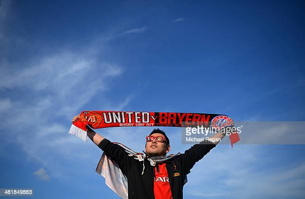 Manchester United fan holds up a matchday scarf ahead of the UEFA Champions League Quarter Final first leg match between Manchester United and FC...