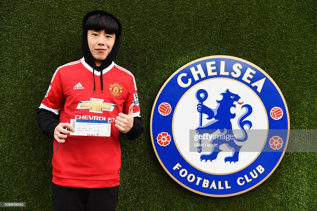 A Manchester United fan poses next to the Chelsea club crest prior to the Barclays Premier League match between Chelsea and Manchester United at Stamford Bridge on February 7, 2016 in London, England.