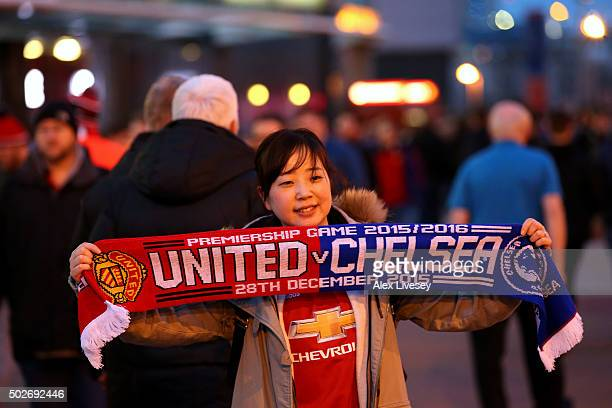 Manchester United fan poses with a scarf outside the stadium before the Barclays Premier League match between Manchester United and Chelsea at Old...